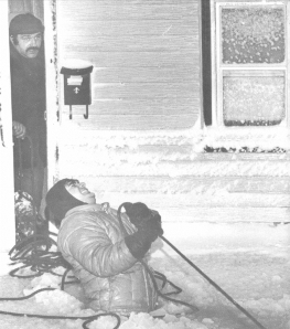 Rescue worker struggles to haul evacuation boat to the front door of this home in Revere, Mass (photograph by Paul Benoit, Boston Herald American).